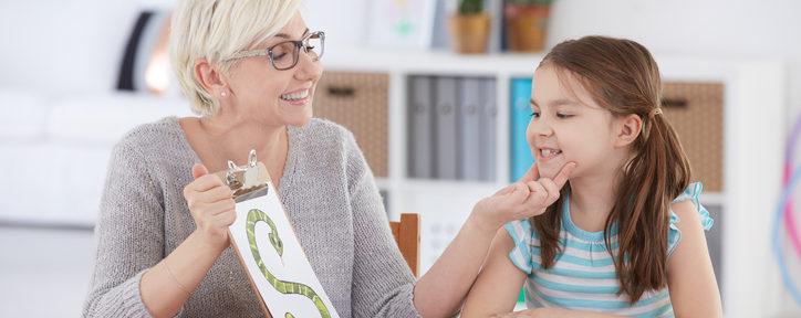 Woman helping teach child who has speech language disorder